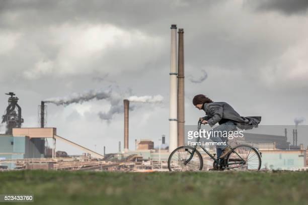 netherlands, ijmuiden, tata steel factory, blast furnaces. cyclist - luchtvervuiling stockfoto's en -beelden