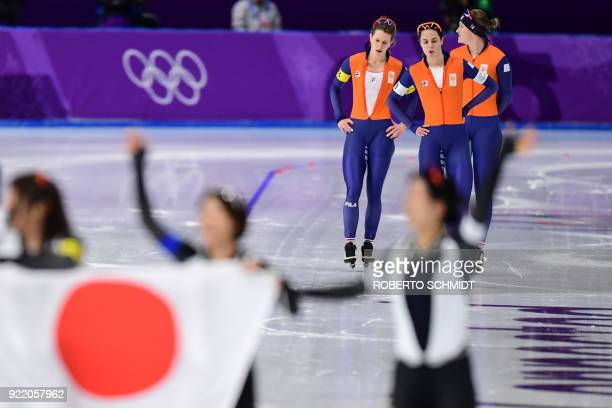 Netherlands' Ireen Wust Netherlands' Marrit Leenstra and Netherlands' Antoinette De Jong reacts after taking silver as the Japanese team celebrate...