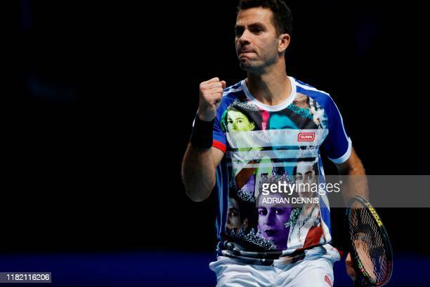 Netherlands' JeanJulien Rojer reacts wearing a Tshirt featuring images of Britain's Queen Elizabeth II as he plays with Romania's Horia Tecau against...