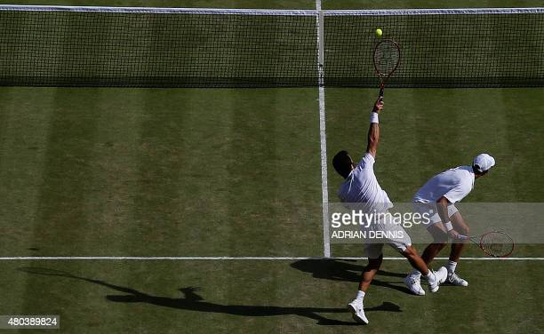 Netherlands' JeanJulien Rojer smashes a return at set point next to his partner Romania's Horia Tecau against Britain's Jamie Murray and his partner...