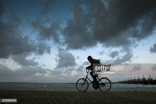 netherlands, kamperland. woman cycles during storm - wind stockfoto's en -beelden
