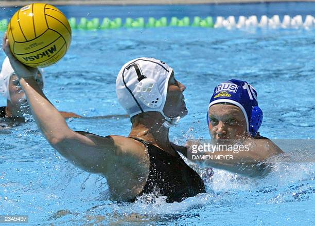 Netherland's Karin Kuipers fights for the ball with Russian Olga Turova during their preliminary match at the 10th World Swimming Championships in...