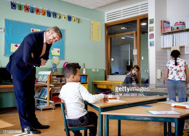 Netherlands' King Willem-Alexander speaks to a child in a class with students of parents with vital professions during a working visit to the primary...