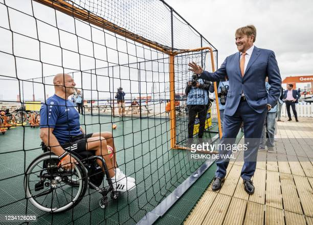 Netherlands' King Willem-Alexander talks with a competitor in a wheelchair during the opening of TeamNL Olympic Festival on the sports beach of The...