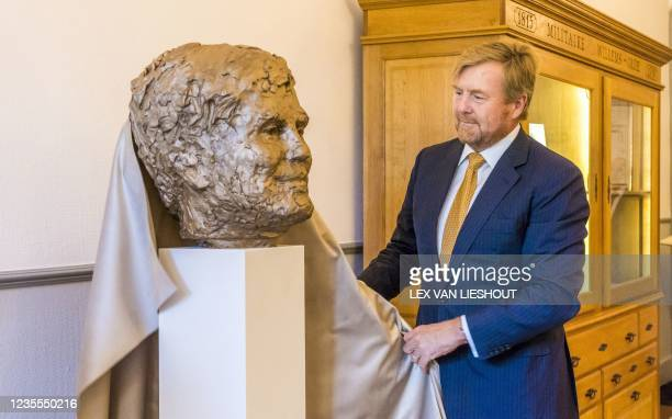Netherlands' King Willem-Alexander unveils a bronze effigy statue by Dutch artist Jikke van Loon during a visit to the Chancellery of the Dutch...
