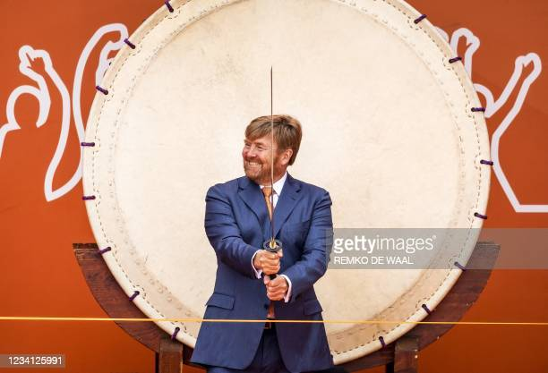 Netherlands' King Willem-Alexander uses a sword to cut a ribbon during the opening of TeamNL Olympic Festival on the sports beach of The Hague on 23...