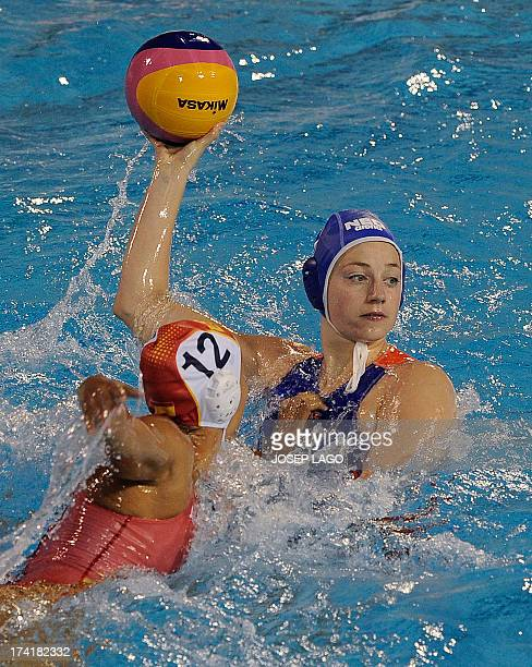 Netherlands' Lefke van Belkum vies with Spain's Laura Lopez during their preliminary round match of the women's water polo competition at the FINA...