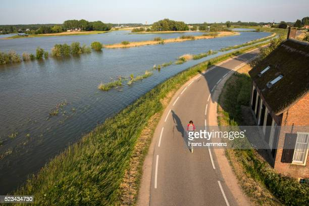 netherlands, lienden, woman cycles on dyke - gelderland stock pictures, royalty-free photos & images