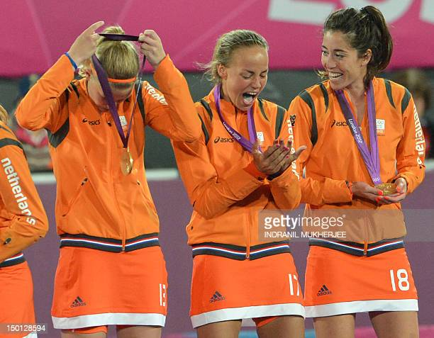 Netherlands Maartje Paumen and teammates Netherlands Naomi van As and Caia van Maasakker show their delight while holding their gold medals as they...