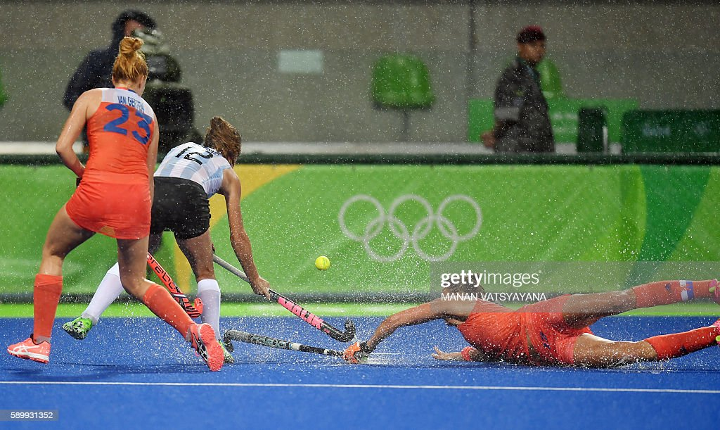 TOPSHOT - Netherlands' Maartje Paumen (R) falls on the pitch as she vies for the ball with Argentina's Delfina Merino during the women's quarterfinal field hockey Netherlands vs Argentina match of the Rio 2016 Olympics Games at the Olympic Hockey Centre in Rio de Janeiro on August 15, 2016. / AFP / MANAN