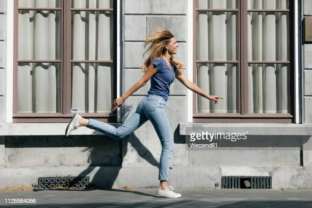 netherlands, maastricht, happy blond young woman running along building in the city - jeans stock pictures, royalty-free photos & images