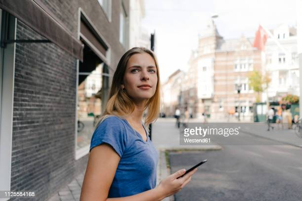 netherlands, maastricht, smiling young woman with cell phone in the city looking around - オランダ リンブルフ州 ストックフォトと画像