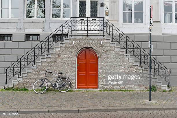 Netherlands, Maastricht, town house with double stairway, bicycle and red door