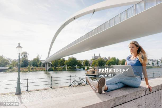 netherlands, maastricht, young woman sitting on a wall at the riverside with laptop - meuse river stock photos and pictures