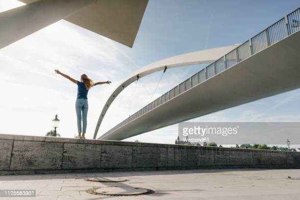 netherlands, maastricht, young woman standing on a wall at a bridge - ausgestreckte arme stock-fotos und bilder