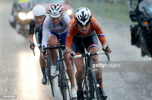 Netherlands' Marianne Vos Russia's Olga Zabelinskaya and Britain's Elizabeth Armitstead cycle during a heavy downpour in the women's cycling road...