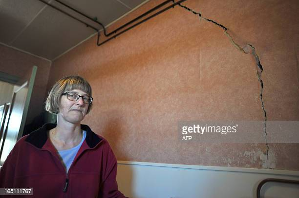 Netherland's Martha Bos poses in front of a crack in her wall on March 12 2013 in Middelstum some 10km from Groningen caused by repeated earthquakes...