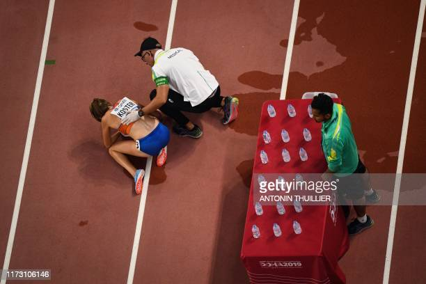 Netherlands' Maureen Koster receives medical attention after falling during the Women's 5000m heats at the 2019 IAAF Athletics World Championships at...