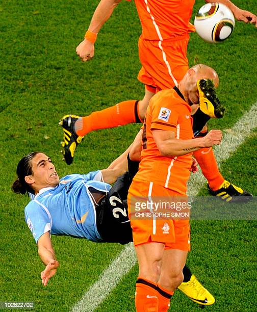 Netherlands' midfielder Demy de Zeeuw is kicked in the face by Uruguay's defender Martin Caceres during the 2010 World Cup semi-final football match...