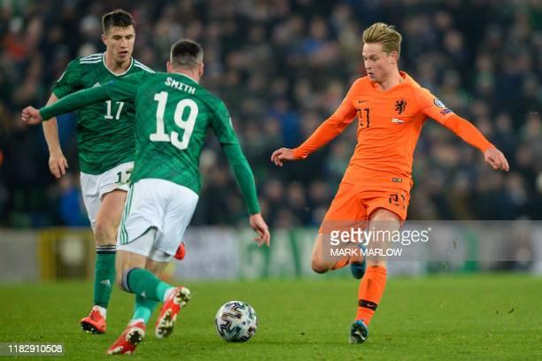 Netherlands' midfielder Frenkie De Jong vies with Northern Ireland's defender Patrick McNair and Northern Ireland's defender Michael Smith during the...