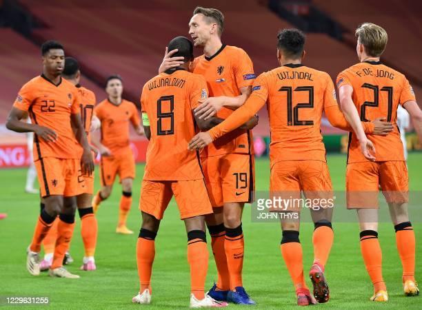 Netherlands' midfielder Georginio Wijnaldum celebrates with Netherlands' forward Luuk de Jong and teammates after scoring the opener during the UEFA...