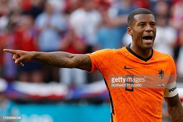 """Netherlands' midfielder Georginio Wijnaldum wearing a captain's armband bearing the words """"One Love"""" and a rainbow motif gestures during the UEFA..."""