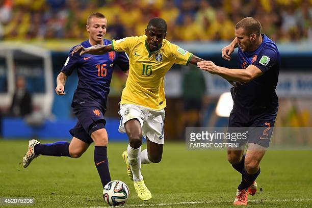 Netherlands' midfielder Jordy Clasie and Netherlands' defender Ron Vlaar challenge Brazil's midfielder Ramires during the third place playoff...