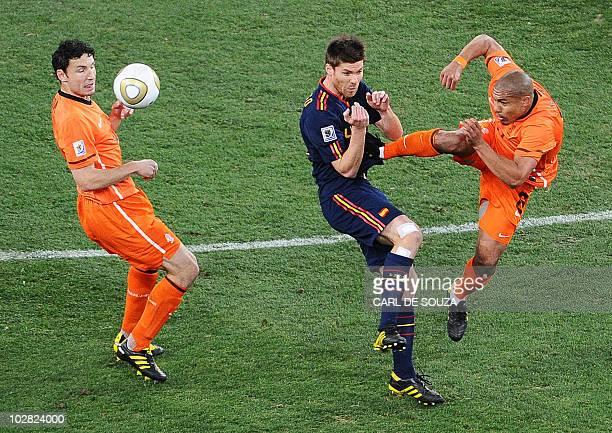 Netherlands' midfielder Nigel de Jong fouls Spain's midfielder Xabi Alonso with a kick to the stomach as Netherlands' midfielder Mark van Bommel...