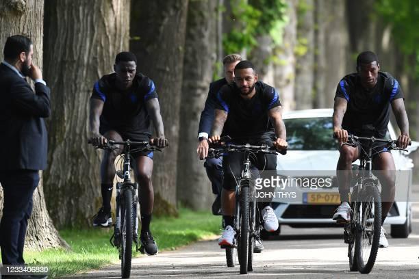 Netherlands' midfielder Quincy Promes, Netherlands' forward Memphis Depay and Netherlands' midfielder Georginio Wijnaldum ride bikes as they leave...