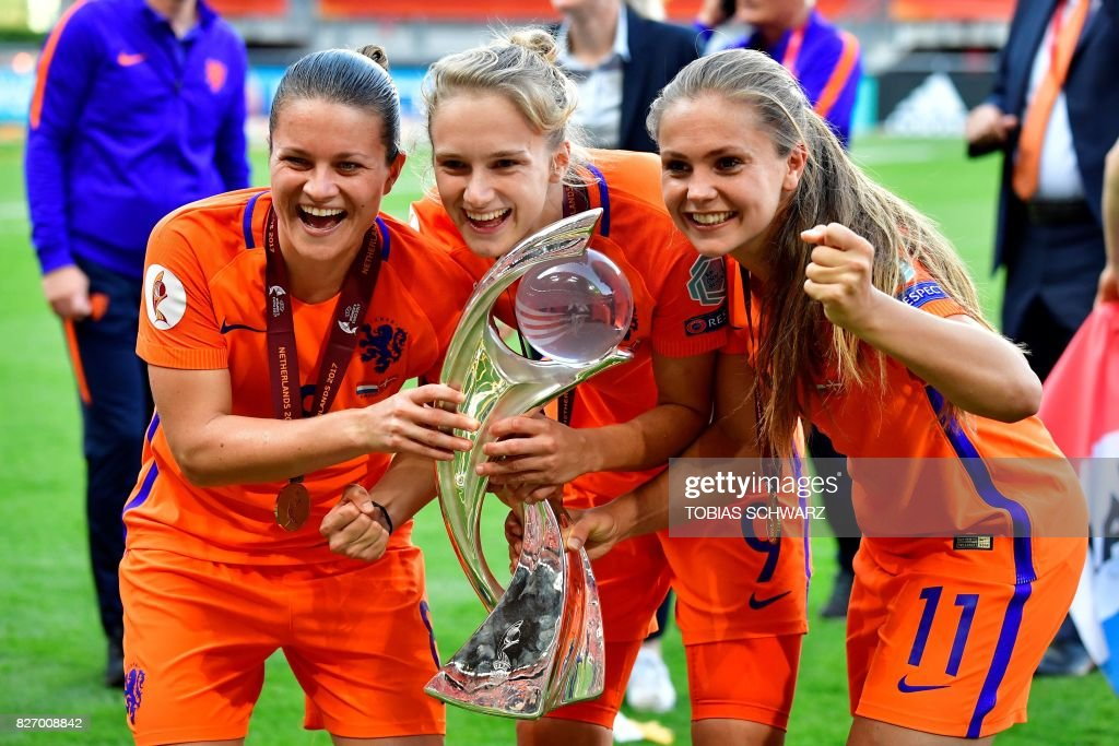 Netherlands' midfielder Sherida Spitse, Netherlands' forward Vivianne Miedema and Netherlands' midfielder Lieke Martens pose together as they celebrate with the trophy after winning with their team the UEFA Womens Euro 2017 football tournament final match between Netherlands and Denmark at Fc Twente Stadium in Enschede on August 6, 2017. / AFP PHOTO / Tobias SCHWARZ