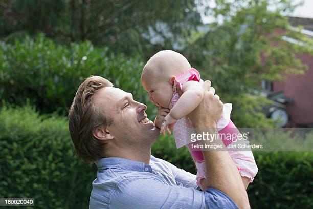 netherlands, mijnsheerenland, father holding baby daughter (6-11 months) in park - mijnsheerenland stock pictures, royalty-free photos & images