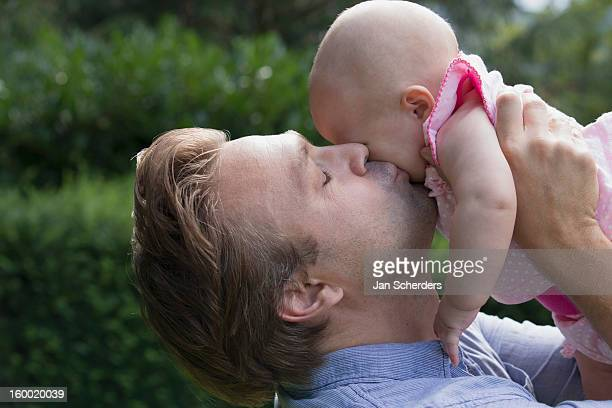 netherlands, mijnsheerenland, father kissing baby daughter (6-11 months) in park - 6 11 months stock pictures, royalty-free photos & images
