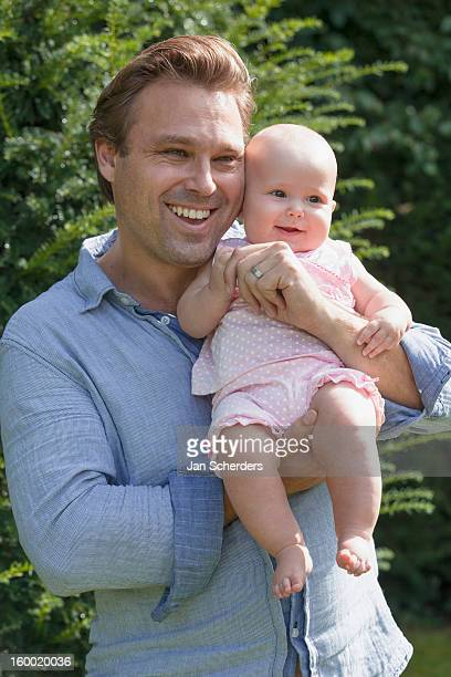 netherlands, mijnsheerenland, father with baby daughter (6-11 months) in park - 6 11 months stock pictures, royalty-free photos & images
