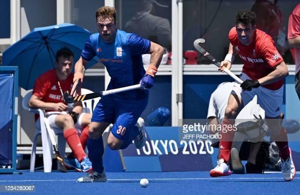 Netherlands' Mink Alphons Louis Van Der Weerden and Britain's Phillip Roper run for the ball during their men's pool B match of the Tokyo 2020...