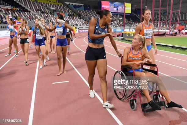 Netherlands' Nadine Broersen in a wheelchair is pushed by France's Solene Ndama after the Women's Heptathlon at the 2019 IAAF Athletics World...