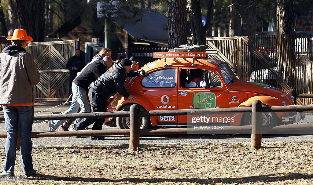 Netherlands' national football team supporters push a car before driving in a convoy of 140 'orange' vehicles from the Fountainvalley camp, northern Johannesburg on June 16, 2010. Around 700 Dutch fans will move from Johannesburg to Durban, the city where their team will play their second 2010 World Cup football match against Japan.
