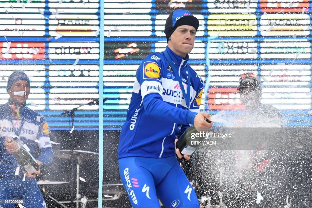 Netherland's Niki Terpstra throws champagne as he celebrates his victory during the podium ceremony of the 61st edition of the 'E3 Prijs Vlaanderen Harelbeke' cycling race, on March 23, 2018 in Harelbeke. / AFP PHOTO / BELGA AND Belga / DIRK WAEM / Belgium OUT