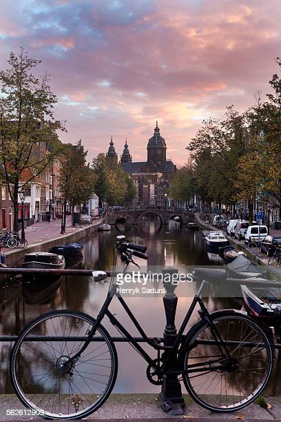 Netherlands, North Holland, Amsterdam, Basilica of st nicholas and bicycle by canal in city