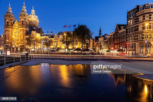 Netherlands, North Holland, Amsterdam, Canal and illuminated buildings at sunrise