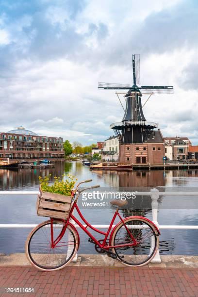 netherlands, north holland, haarlem, bicycle parked along railing of canal bridgewith de adriaan windmill in background - niederlande stock-fotos und bilder