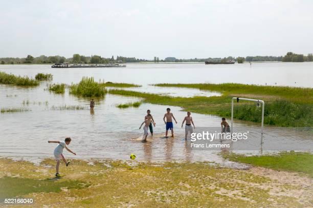 Netherlands, Ochten, Boys Play Football In Flooded Floodplains