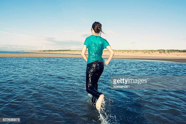 Netherlands, Ouddorp, Teenage girl running on beach
