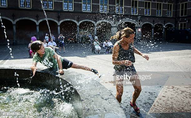 **netherlands out A mother and her son play with a water fountain during the hot weather on July 3 2015 at the Binnenhof in the Hague AFP PHOTO / ANP...