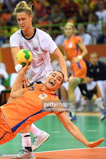 Netherlands' pivot Yvette Broch falls as she shoots past Norway's pivot Marit Malm Frajford during the women's Bronze Medal handball match...