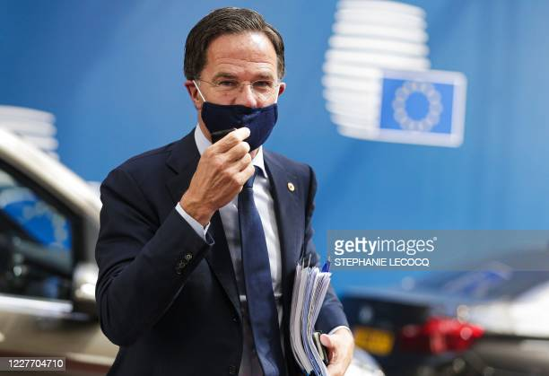 Netherlands' Prime Minister Mark Rutte adjusts his protective face mask as he arrives for the fourth day of an EU summit at the European Council...