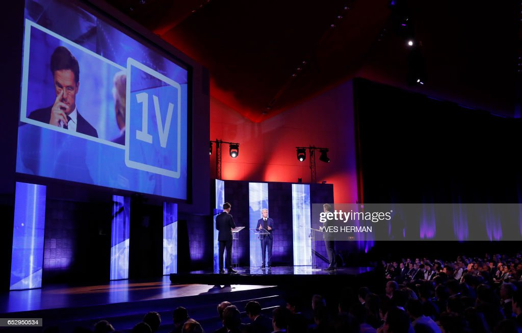 Netherlands' prime minister Mark Rutte (L) of the VVD Liberal party debates onstage with Netherlands' far-right politician Geert Wilders (C) of the PVV party on March 13, 2017 in Rotterdam, prior to March 15 Dutch parliamentary elections. /