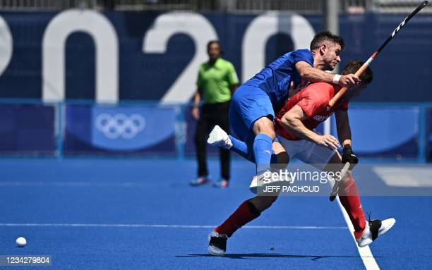 Netherlands' Robbert Kemperman collides with Britain's Liam Sanford during their men's pool B match of the Tokyo 2020 Olympic Games field hockey...