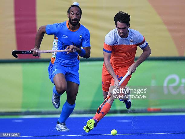 Netherland's Robert van der Horst controls the ball as India's Sardar Singh chases during the men's field hockey Netherland's vs India match of the...
