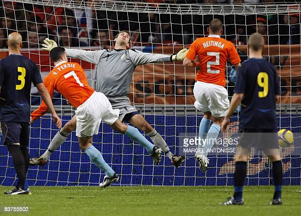 Netherland's Robin van Persie heads the ball to score the opening goal past Sweden's goalkeeper Andreas Isaksson during their friendly match in...