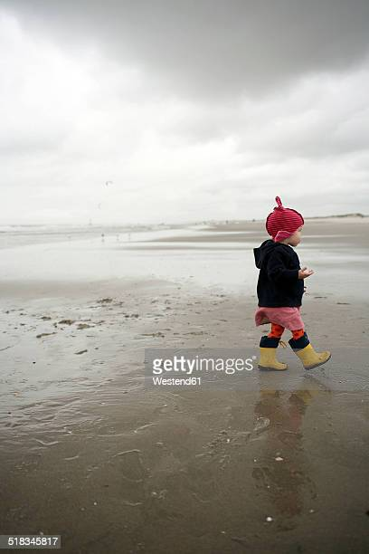 Netherlands, Rotterdam, little girl with red cap and yellow rubber boots walking on the wet sandy beach